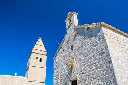 Ancient coastal town of Lubenice on the island of Cres in Croatia, old stone church and tower bell 免版税图像