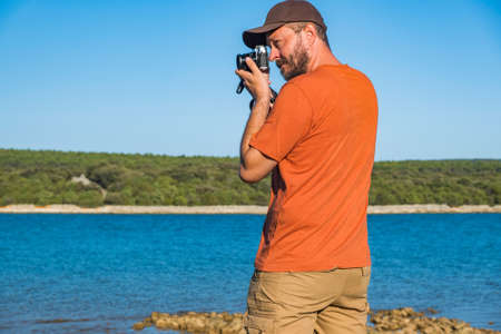Photographer in t-shirt and cargo pants walking around sea shore with mirror less camera, shooting nature, half body portrait, landscape photography concept