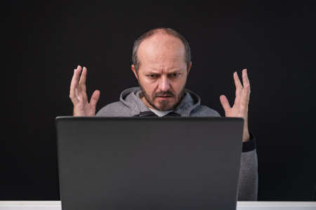 Man working from home office, angry face expression. Adult bearded sitting behind desk on black background, angry face, having business problem.