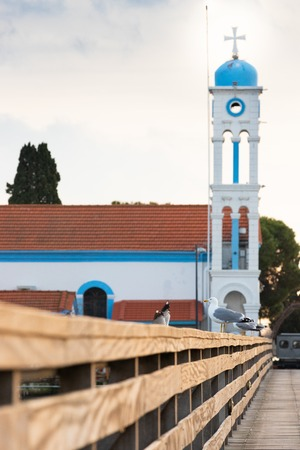 Bell tower of Saint Nicholas monastery in Porto Lagos, Xanthi, Greece. Seagulls standing on the wooden fence.