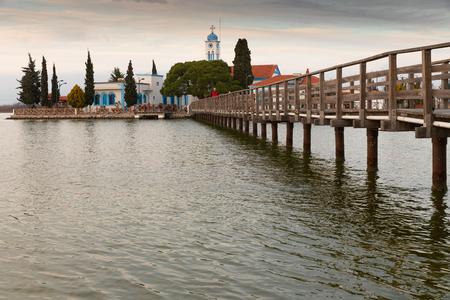 Man crossing a wooden bridge leading to Saint Nicholas monastery in Porto Lagos, Xanthi, Greece Stock Photo