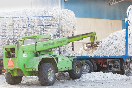 Tractor trolley full of seed cotton gets unloaded in the ginning mill in Greece