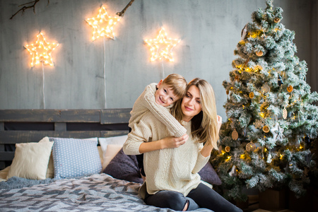 Happy family portrait of mother and baby boy sitting on cosy bed in festivaly decorated room with Christmass tree and shining stars on the wall. New Year`s celebration.
