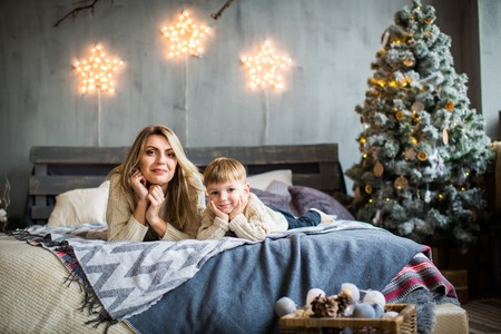 Happy family portrait of mother and baby boy laying on cosy bed in festivaly decorated room with Christmass tree and shining stars on the wall. New Year`s celebration. Reklamní fotografie