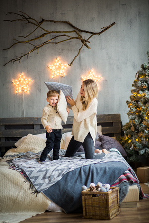 Happy family portrait of mother and baby boy playing with pillows on cosy bed in festivaly decorated room with Christmass tree and shining stars on the wall. New Year`s celebration.