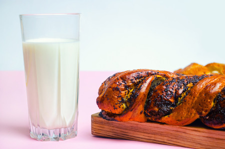 Bun with poppy seeds and a glass of milk on white background, isolate, selective focus     Stock Photo