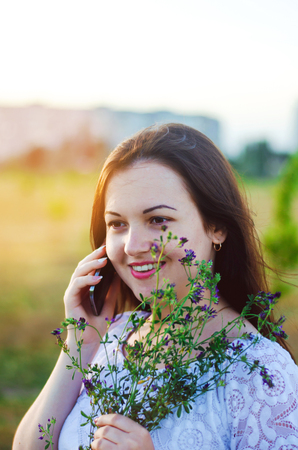 happy young brunette woman talking on the phone with flowers in her hands and smiling. portrait. close-up photo