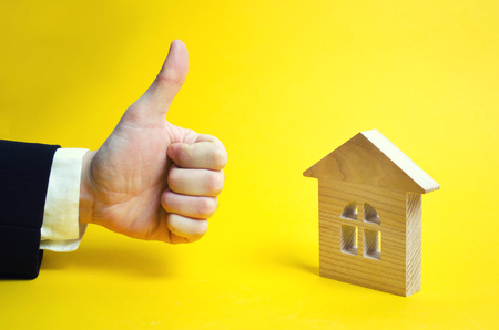 Finger up and house. Wooden house and approving hand. A businessman in a suit gives a good appraisal to the business. Real estate, good make, excellent price. Yellow background. Stock Photo