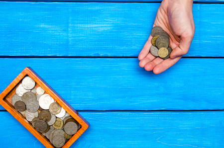 money in hand, casket with coins on a blue wooden background,  space for text