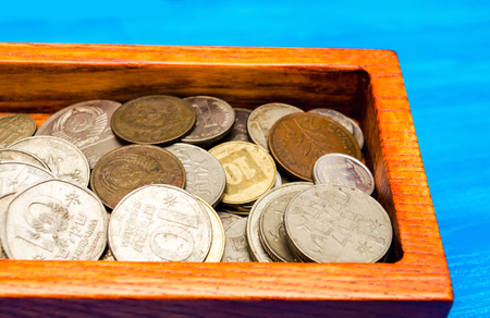 box with coins of countries of the world on a blue wooden background. money. a Palestinian, a Soviet, an Israeli, a Ukrainian coin