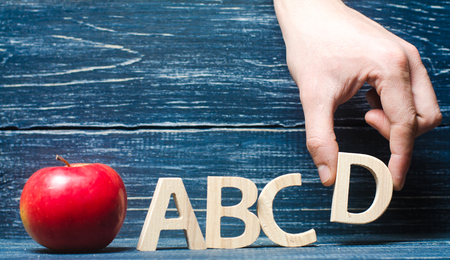Red apple and letters ABCD. The hand puts the letter D in the alphabet order. Apple for the teacher. The concept of teaching and education. School, college, kindergarten, university. Primary school. On a dark background. Stock Photo