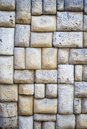 The texture of the stone wall. Stone in the section. Limestone. Granite. Marble. Coquina. Background. Stone floor. Pebbles. Macadam. Banco de Imagens