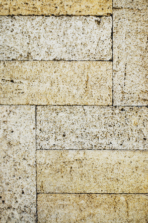 The texture of the stone wall. Stone in the section. Limestone. Granite. Marble. Coquina. Background. Stone floor. Pebbles. Macadam. Imagens