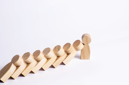 People in line fall like dominoes. Man stops the fall of people as dominoes. The concept of durability and strength, business ideas. Willpower, strong nerves, strong character. Stubbornness. Banco de Imagens