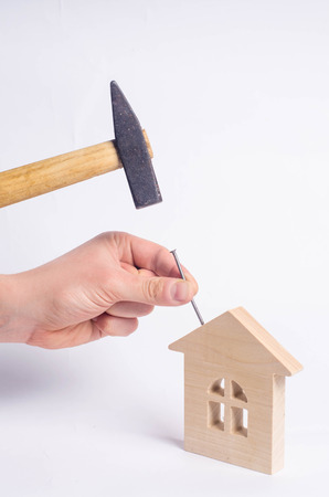 Man hammers a nail with a hammer in a miniature wooden house on a white background. Concept of repair of houses. The worker conducts repair work at the facility, in the residential building. A hammer, a nail, a small house. Stock Photo