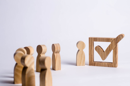 Three wooden human figures stand together next to a tick in the box. The concept of elections and social technologies. Volunteers, parties, candidates, constituency electorates. Human rights. Stock Photo