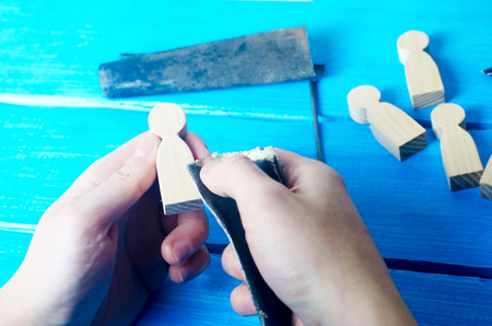 The master processes the wood with his hands. Working hands on a blue background with tools. Creation of domestic crafts made of wood. Small wooden figures of people. Concept work yourself. DIY