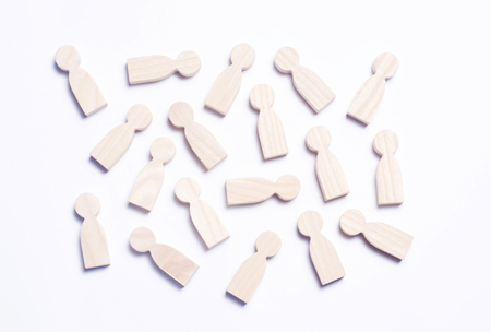 Wooden figures of people on a white background. The concept of society, collective, company, family, neighbors. A crowd of people at a meeting, rally. Statistical data. Workers, employees