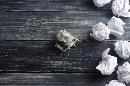 A crumpled dollar on a table next to white paper balls. The process of thinking and finding new business ideas, profitable solutions. Attraction of investments and creation of business