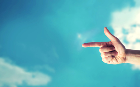 finger pointing at something and blue sky, place for text Stock Photo