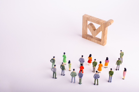 human figures stand together next to a tick in the box. The concept of elections and social technologies. Volunteers, parties, candidates, constituency electorates. Human rights Selective focus Banque d'images - 101198047