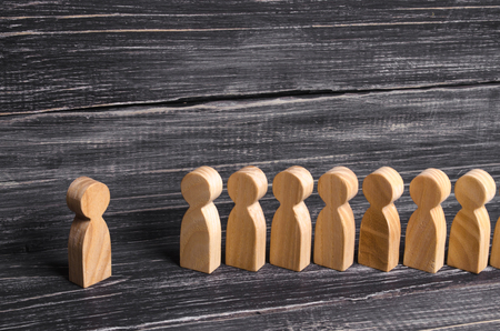 People stand in line at the briefing and wait for orders. Wooden figures of people are waiting in line. Concept of business, army, sports team. People listen to a mentor. Obedience and discipline.