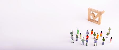 menschliche Figuren stehen neben einem Häkchen in der Box zusammen. Das Konzept von Wahlen und sozialen Technologien. Freiwillige, Parteien, Kandidaten, Wahlkreiswähler. Selektives Fokusbanner