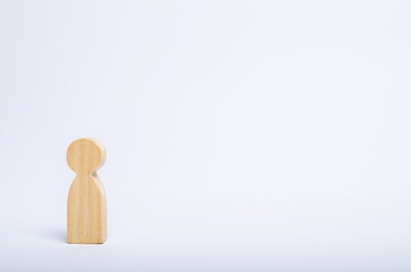 A lone wooden human figure stands on a white background. A person is waiting, standing and waiting. Style of minimalism, space for text