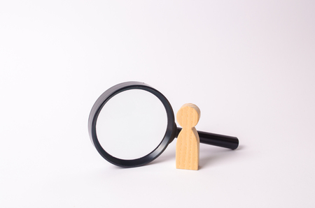A wooden human figure stands near a magnifying glass on a white background. The concept of the search for people and workers. Search for vacancies and work. Human resources, management. 写真素材