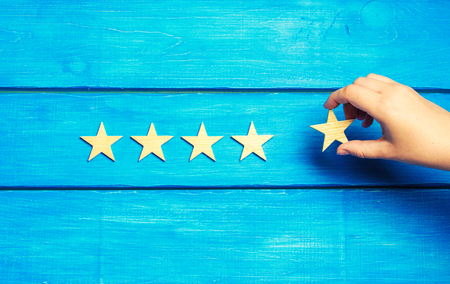 A womans hand puts the fifth star. Quality status is five stars. A new star, achievement, universal recognition.The critic determines the rating of the restaurant, hotel, institution. Quality mark.
