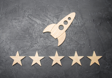 A wooden space rocket and five stars on a concrete background. The concept of space travel, commercial launches into space. Imagens