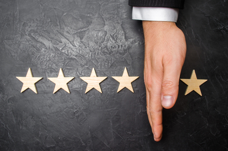 The hand of the businessman separates the fifth star from the other four. The loss of the fifth star, the fall in rating and recognition.