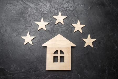 Wooden house and five stars on a gray background. Rating of houses and private property. Buying and selling, renting apartments.