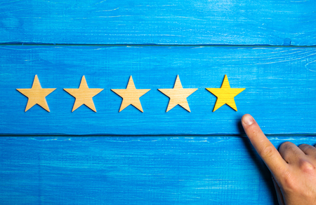 The male hand points to the fifth yellow star on a blue wooden background. Five Stars. Rating of restaurant or hotel, application.