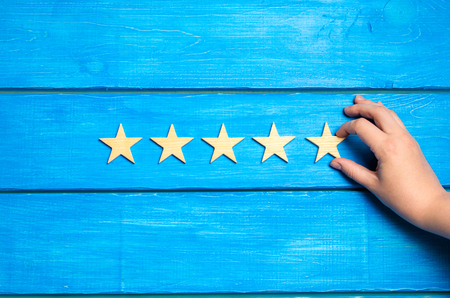 The hand puts the fifth star. The critic determines the rating of the restaurant, hotel, institution. Standard-Bild