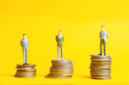 People stand on columns of coins. The concept of career growth, the rate of deposit. Customer loyalty program. Business growth, profit increase, business reputation Archivio Fotografico