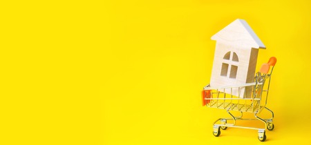 Property investment and house mortgage financial concept. buying, renting and selling apartments. real estate. Wooden house in a Supermarket trolley. credit, affordable housing for young families. place for text. banner Stockfoto