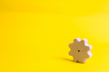 A wooden gear on a yellow background. The concept of technology and business processes. Minimalism. Mechanisms and devices. Work, moving forward. Development and development. Stock Photo