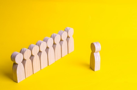 People listen to the leader. People stand in line at the briefing and wait for orders. Wooden figures of people are waiting in line. Concept of business, army, sports team. Obedience and discipline