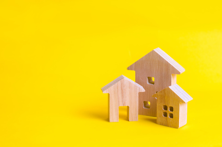 Three houses on a yellow background. Buying and selling of real estate, construction. Apartments and apartments. City, settlement. Minimalism. for presentations. real estate market.