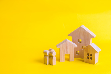 People and three houses on a yellow background. Buying and selling of real estate, construction. Apartments and apartments. City, settlement. Minimalism. for presentations. real estate market.