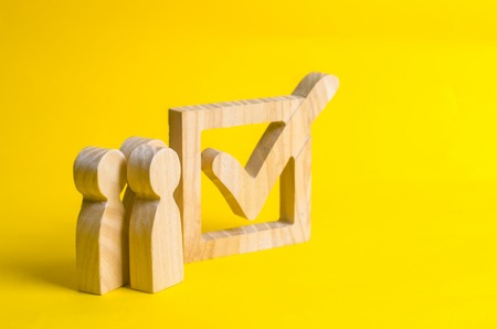People stand near a wooden checkmark in a box on a yellow background. The concept of suffrage, voting in elections. Election of the President or Government. Democracy, development, civil initiative. Stock Photo