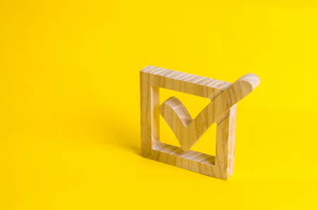 A wooden checkmark in the box on a yellow background. The concept of suffrage, voting in elections. Election of the President or Government. Democracy, development, civil initiative. Stock Photo