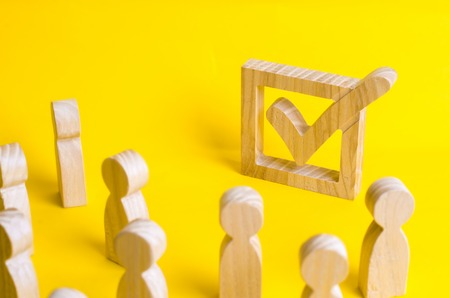 A group of wooden figures of people surround and look at a tick in the box. Voters take part in elections. Voting, referendum, social survey. Statistical data. Democratic process, institutions.