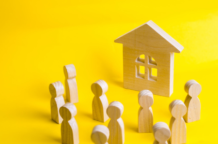 A group of wooden figures of people surround and look at the wooden house. Young people in search of affordable housing. Loans and loans for the purchase of a new home. Rent.