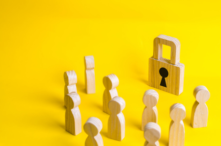 A group of wooden figures of people surround and look at the padlock. The concept of protecting personal data in social networks. Leakage of private data to the network. Security and protection.