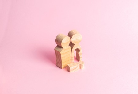 Wooden figures of a man and a woman with a void inside the body in the form of a child. Infertility in a couple. Loss of a single child. Medical problems. Dead baby. Tragedy in the family