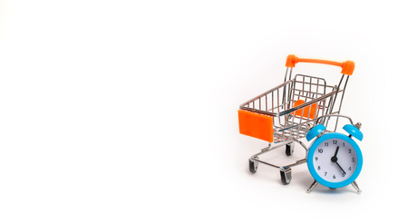 A blue alarm clock and a wheelbarrow on a white background. The concept of shopping, sale. The limited edition is already on sale. Marketing and business, time planning. Minimalism.