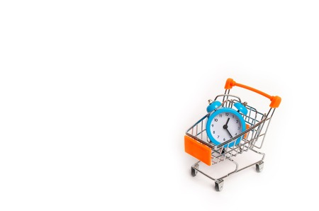 The limited edition is already on sale. Marketing and business, time planning. Minimalism. A blue alarm clock and a wheelbarrow on a white background. The concept of shopping, sale.