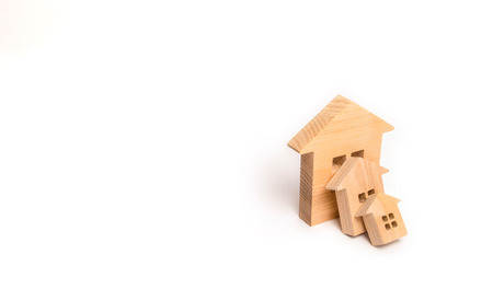 Small wooden houses fall on the big house as a domino. The concept of buying real estate. Insurance and investment risk. Falling prices in the real estate market. Growth in demand. Catastrophe. Banco de Imagens